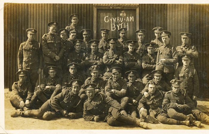 ADX/375/11 Postcard of a Welsh regiment with 'Cymru am Byth' painted on the wall behind them, sent to Mrs D. H. Davies of The Eagle, Cardigan.