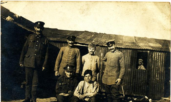 ADX/375/15 Postcard showing Major Harton Davies (bottom left) and six other soldiers in a German prisoner of war camp.