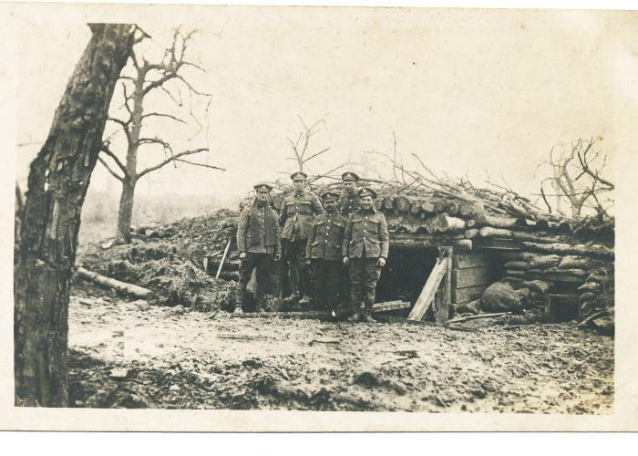 ADX/375/2 Photograph of five soldiers outside a dug-out on the front line during the First World War.