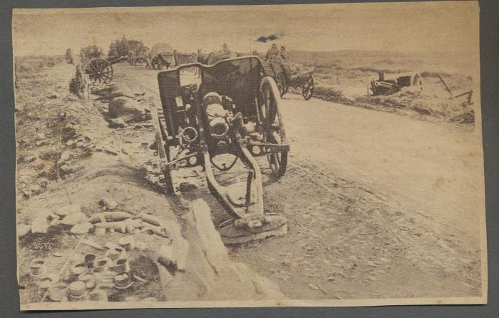 ADX/375/34 Newspaper cutting showing cannons, dead horses and soldiers on the front line during First World War